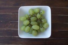 Zieleni winogrona w białym pucharze na drewnie od above Zdjęcie Stock