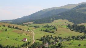 Zieleni wzgórza i chałupa z czerwień dachem blisko wioski zbiory wideo