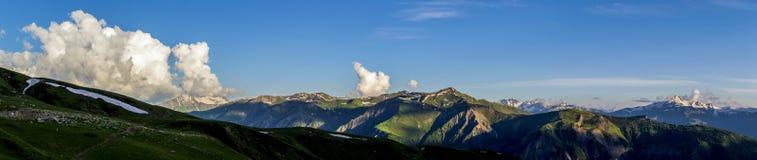 Zieleni wzgórza z śniegiem na szczytach w wieczór świetle słonecznym obrazy royalty free