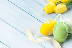 Zielenie barwiący Easter jajka z żółtym kwiatem na błękitnym drewnianym baclgrund obrazy royalty free