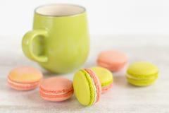 Zielenieje kolorowych macaroons z zielonym kubkiem i różowi Zdjęcia Stock