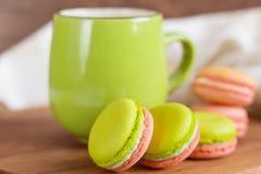Zielenieje kolorowych macaroons z zielonym kubkiem i różowi Fotografia Stock