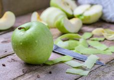 Zielenieje obranego jabłka na naturalnym nieociosanym drewnianym tle Fotografia Stock