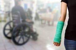 Zielenieje obsadę na ręce i ręce na zamazanym tło pacjenta obsiadaniu Zdjęcia Stock