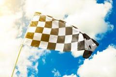 Zielflagge, die in den Wind mit dem Sonnenaufflackern gesehen wellenartig bewegt Stockfotos