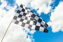Zielflagge, die in den Wind - Wolken auf Hintergrund wellenartig bewegt stockfotografie