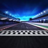 Ziellinie auf der Rennbahn in der Bewegungsunschärfe mit Stadion und Scheinwerfern Stockfoto