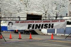 Zielliniefahne dehnte über die Straße bei jährlichem Christopher Dailey Turkey Trot, Saratoga Springs, New York, 2014 aus Stockfotografie