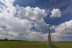 Zielona łąka z wiejską drogą, chmurami i ogrodzeniem na przedpolu, Zdjęcia Stock