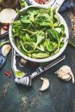 Zielona świeża organicznie sałata opuszcza w starym emaliującym colander na ciemnym nieociosanym kuchennym stole z narzędziami i  Obrazy Royalty Free