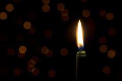 Zielona świeczka z płomieniem i bokeh w tle Obrazy Stock