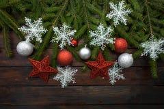 Zielona żywa świerczyna rozgałęzia się na ciemnym drewnianym tle Nowego Roku tło z białymi czerwieni gwiazdy, płatkami śniegu i p Fotografia Royalty Free