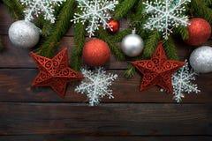 Zielona żywa świerczyna rozgałęzia się na ciemnym drewnianym tle Nowego Roku tło z białymi czerwieni gwiazdy, płatkami śniegu i p Obraz Royalty Free