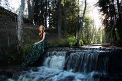 Zielona boginki spojrzenia kobieta blisko siklawy w lesie Fotografia Stock