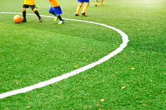 Zielona boisko do piłki nożnej trawa z białą oceny linią i chłopiec bawić się futbolowego tło Obrazy Stock
