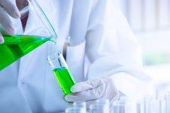 Zielona ciekła substancja nalewał w próbną tubkę obrazy stock