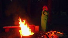 Zielona czarownica Widzii grże ogieniem przy nocą w lesie someone zakrywa jego twarz zdjęcie wideo
