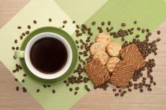Zielona filiżanka kawy na fasole, stole i ciastko i najlepszy widok Zdjęcia Stock