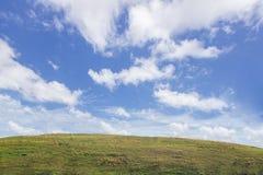 Zielona góra, niebieskie niebo i chmurny tło, obrazy stock