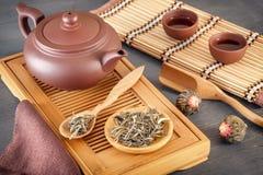 Zielona herbata i atrybuty dla herbacianej ceremonii - ceramiczny teapot, filiżanki, durszlak, chopsticks i pincety, umieszczamy zdjęcie royalty free