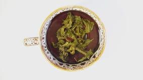Zielona herbata warzą w ciemnej filiżanki suchych płatkach rozwija się w wodnym czasu upływu wideo zdjęcie wideo