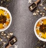 Zielona Jaśminowa herbata z świeżymi kwiatami i herbaciane filiżanki na czerni drylujemy tło, rama, odgórny widok Fotografia Stock