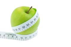 Zielona jabłko miara wokoło talii na białym backgrou Obrazy Royalty Free