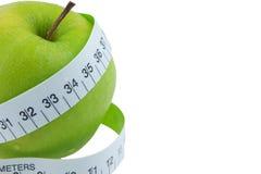 Zielona jabłko miara wokoło talii na białym backgrou Zdjęcie Stock