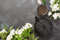 Zielona jasmin herbata i jaśminowi kwiaty, filiżanka zielona herbata na czerni Odgórny widok teatime Zdjęcie Stock