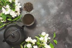 Zielona jasmin herbata i jaśminowi kwiaty, filiżanka zielona herbata na czerni Odgórny widok teatime Obrazy Stock