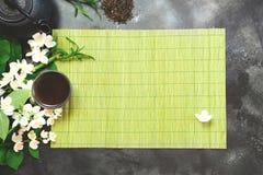 Zielona jasmin herbata i jaśminowi kwiaty, filiżanka zielona herbata na czerni Odgórny widok teatime Fotografia Stock