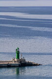 Zielona latarnia morska na błękitnym tle Fotografia Royalty Free