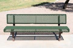 Zielona metal ławka w parku na betonie zdjęcia royalty free
