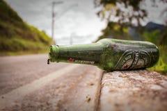 Zielona piwna butelka na krawężniku zdjęcie royalty free