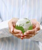 Zielona planeta w women&-39; s ręki Obrazy Royalty Free