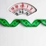 Zielona pomiarowa taśma na ciężar skala dietetyczka Fotografia Stock