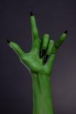 Zielona ręka z czarnymi gwoździami pokazuje ciężkiego metal gestykuluje Zdjęcie Stock