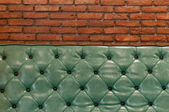 Zielona retro leżanka w żywym pokoju z cegły ścianą behind Fotografia Stock