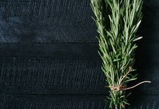 Zielona rozmarynowa wiązka na czarnego rocznika tła drewnianym zakończeniu w górę odgórnego widoku, naturalny organicznie aromaty obrazy royalty free