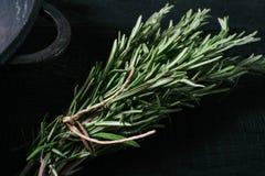 Zielona rozmarynowa wiązka na czarnego rocznika tła drewnianym zakończeniu w górę odgórnego widoku, naturalny organicznie aromaty obraz stock