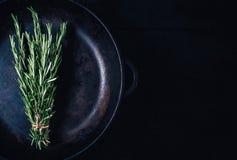 Zielona rozmarynowa wiązka na czarnego rocznika tła drewnianym zakończeniu w górę odgórnego widoku, naturalny organicznie aromaty zdjęcia royalty free