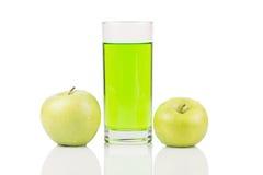 Zielona sok pozycja między dwa zielonymi jabłkami z wodą opuszcza na powierzchni na białym tle Fotografia Royalty Free