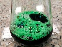 Zielona substancja chemiczna w Erlenmeyer kolbie Eksperyment, gulgocze chemiczną reakcję fotografia stock