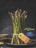 Zielona szparagowa wiązka z pustą etykietki pozycją na ciemnym kuchennym stole Fotografia Royalty Free
