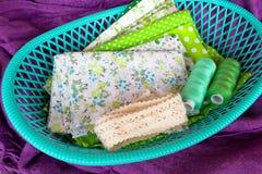 Zielona tkanina, koronka i nić w zielonym pudełku na purpurowym tle, Fotografia Royalty Free