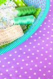 Zielona tkanina, koronka i nić w zielonym pudełku na purpurowym tle, Obrazy Royalty Free
