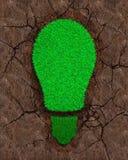 Zielona trawa w formie żarówki na suchej czerwieni ziemi z pęknięcia tłem, pojęciem ECO i energią odnawialną, fotografia stock