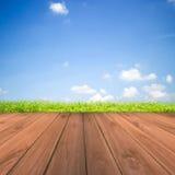 Zielona trawa z niebieskiego nieba i drewna podłoga tłem Obraz Royalty Free