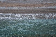 Zielona woda przy otoczak plażą Zdjęcie Royalty Free