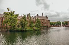 Zielona wyspa na Hofvijver jeziorze z Binnenhof Gockimi rządowymi budynkami chmurnym niebem w Haga i Zdjęcia Royalty Free